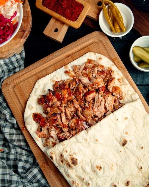 Hühner-döner-kebab im fladenbrot, serviert mit eingelegter gurke und pfeffer Kostenlose Fotos