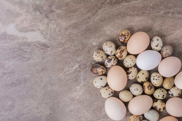 Hühner- und wachteleier auf dem boden Kostenlose Fotos