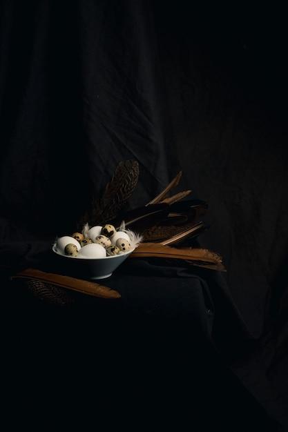 Hühner- und wachteleier zwischen federn in der schüssel nahe großen spulen Kostenlose Fotos