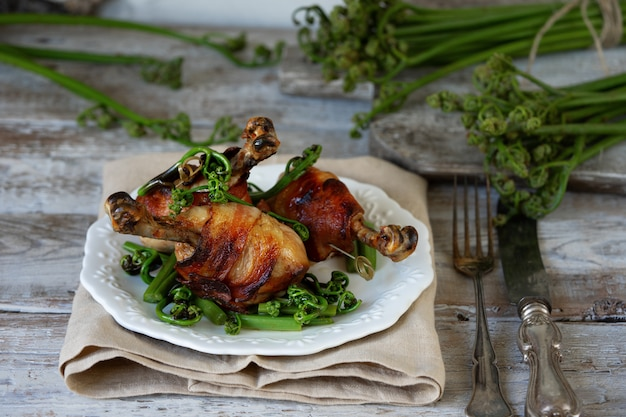 Hühnerbeine im speck und im gebratenen adlerfarn auf einer weinleseplatte. Premium Fotos