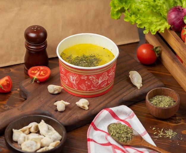 Hühnerbrühe mit kräutersuppe in der wegwerfschalenschüssel diente mit grünem gemüse. Kostenlose Fotos