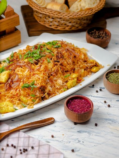 Hühnerbrust, tomatensauce, reis, risotto, plov mit kräutern, joghurt und sumakh in der weißen platte Kostenlose Fotos