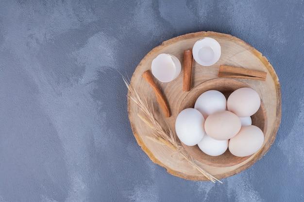 Hühnereier mit eierschalen auf holzplatte Kostenlose Fotos