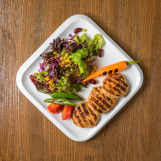 Hühnerfiletcotlets der draufsicht mit grünem salat und karotte. Kostenlose Fotos