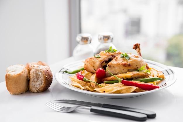 Hühnerfleisch, garniert mit gemüse neben brot Kostenlose Fotos