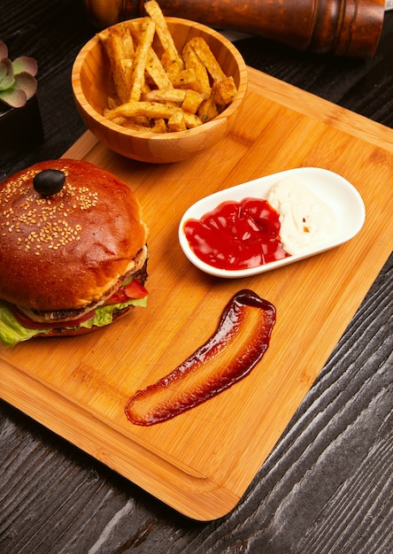 Hühnerfleischburger mit tomate und kopfsalat nach innen und pommes-frites dienten mit schwarzer olive und ketschup auf einem hölzernen behälter Kostenlose Fotos