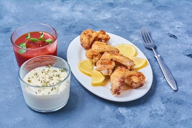 Hühnerflügel gebraten und mit saucen serviert. Kostenlose Fotos