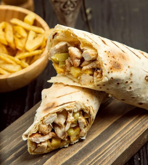 Hühnermurum, shaurma mit lavash und pommes-frites auf hölzernem brett Kostenlose Fotos