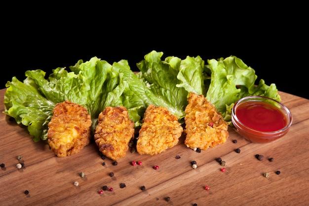 Hühnernuggets, auf einem holztisch mit soße und kopfsalat auf schwarzem hintergrund. Premium Fotos