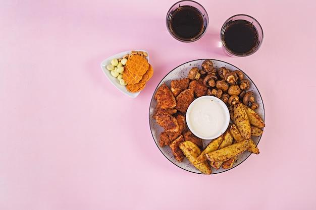 Hühnernuggets mit ketchup, pommes frites, gebackenen pilzen und cola. Premium Fotos