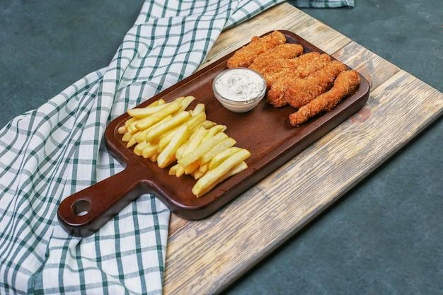 Hühnernuggets mit pommes frites und einem weißen dressing. Kostenlose Fotos