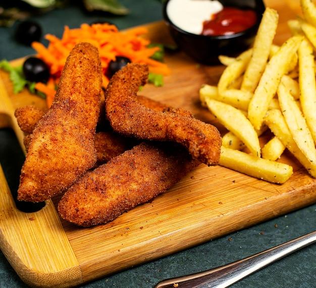 Hühnernuggets nach kfc-art mit pommes frites, mayonnaise, ketchup und gemüsesalat Kostenlose Fotos