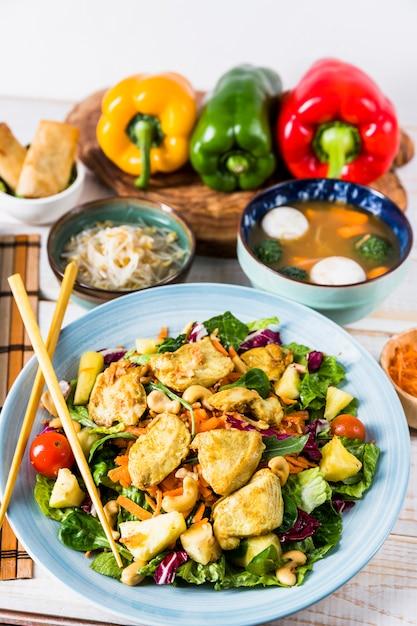 Hühnersalat mit essstäbchen; bohnensprossen- und fischballsuppe auf tabelle Kostenlose Fotos