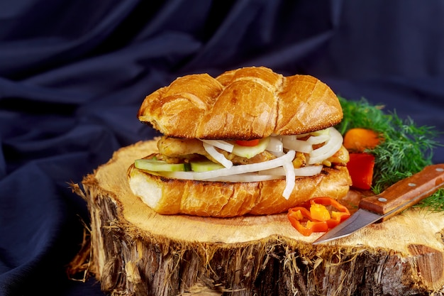 Hühnersandwich mit zwiebeltomatengurke auf einem hölzernen stand Premium Fotos