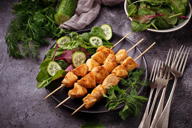 Hühnerschaschenkebabs mit grünem salat. selektiver fokus Premium Fotos