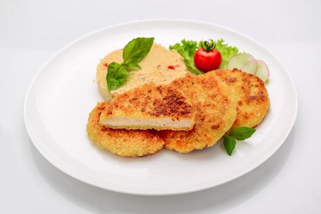 Hühnerschnitzel im teig mit bulgur auf weißem hintergrund Premium Fotos