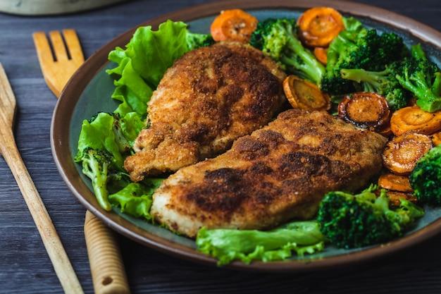 Hühnersteak in den brotkrumen mit gemüse auf einer platte Premium Fotos