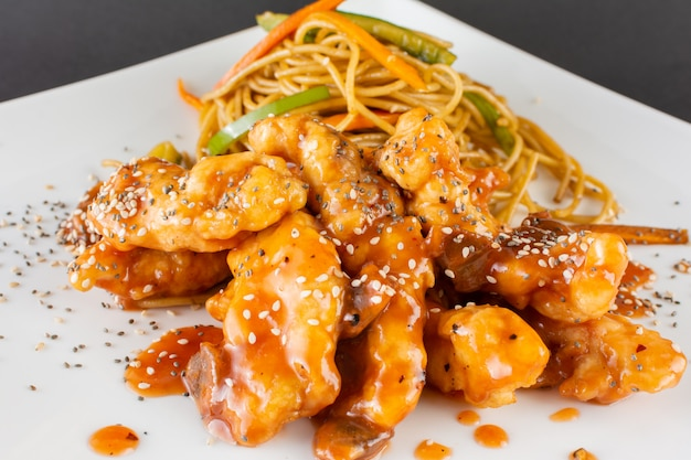 Hühnerstreifen mit tamarindensauce und sautierten tagliatelle Premium Fotos