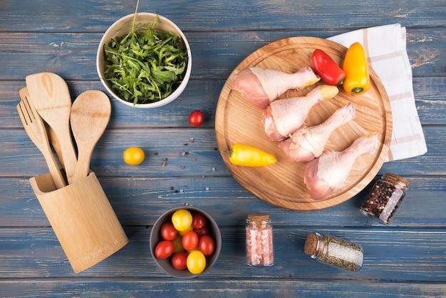 Hühnertrommelstöcke der flachen lage auf hölzernem brett mit pfeffern und tomaten Kostenlose Fotos