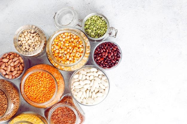 Hülsenfrüchte und bohnensortiment in verschiedenen schalen auf hellem stein. draufsicht. gesunde vegane eiweißnahrung. Kostenlose Fotos