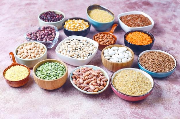 Hülsenfrüchte und bohnensortiment in verschiedenen schalen auf heller steinoberfläche. draufsicht. gesunde vegane eiweißnahrung. Kostenlose Fotos