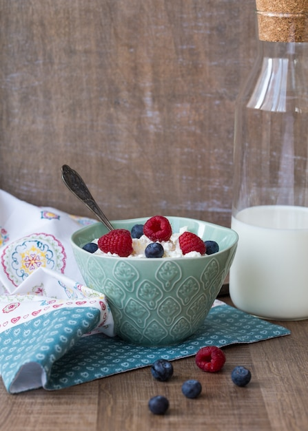 Hüttenkäse in der blauen schüssel mit himbeeren und blaubeeren und milch auf hölzernem hintergrund. gesundes frühstück Premium Fotos