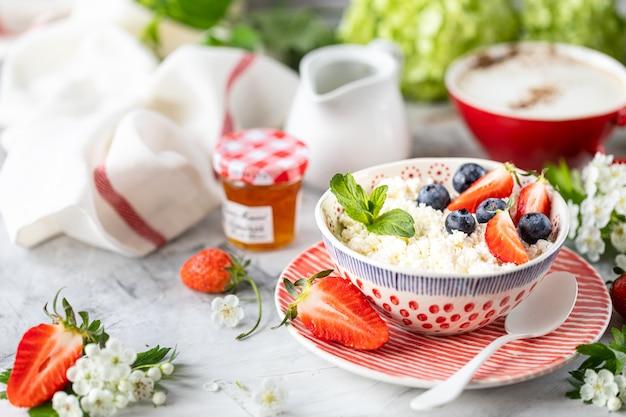 Hüttenkäse mit beeren, marmelade, frischen erdbeeren und einer tasse kaffee mit sahne zum frühstück. Premium Fotos