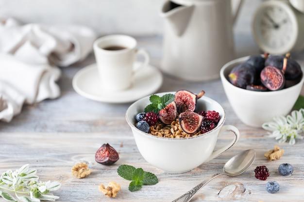 Hüttenkäse mit feigen, beeren, honig. tasse kaffee und kaffeekanne. frühstück. holztisch. Premium Fotos