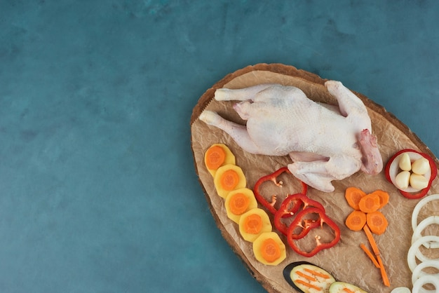 Huhn auf einer holzplatte mit gemüse. Kostenlose Fotos