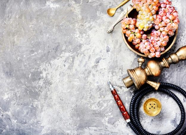 Huka mit aromatrauben auf konkretem hintergrund Premium Fotos