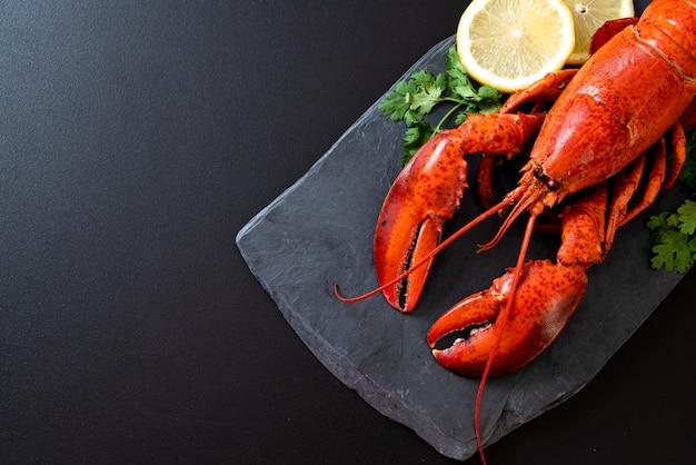 Hummer mit Gemüse und Zitrone auf schwarzem Schiefer Teller Premium Fotos