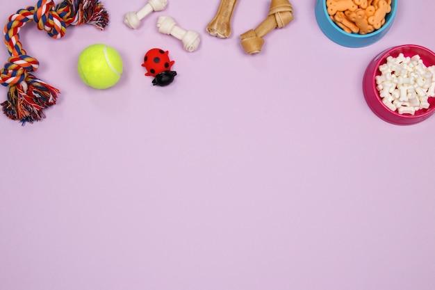 Hundezubehör, -nahrung und -spielzeug auf purpurrotem hintergrund. flach legen. draufsicht. Premium Fotos