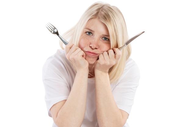 Hungrige umgekippte junge frau mit einer gabel und einem messer in ihren händen, die an einem leeren tisch sitzen. isoliert auf weißem hintergrund Premium Fotos