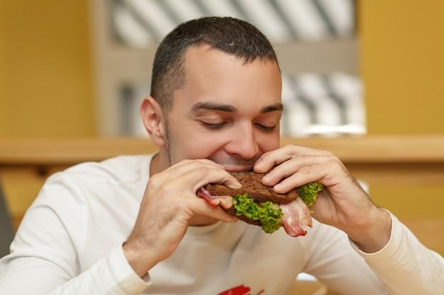 Hungriger junger mann im restaurant essen sandwich Premium Fotos