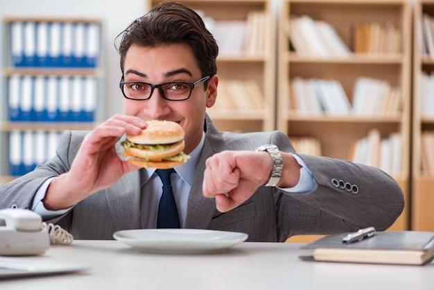 Hungriger lustiger geschäftsmann, der sandwich der ungesunden fertigkost isst Premium Fotos