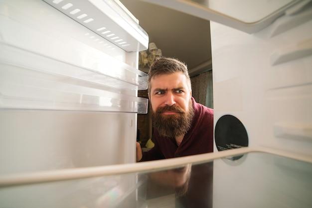 Hungriger mann, der nach nahrung im leeren kühlschrank sucht. bärtiger mann, der in leeren kühlschrank schaut. verwirrter mann in der küche. Premium Fotos