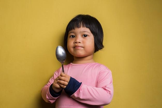 Hungriges asiatisches mädchen, das einen löffel auf gelber wand hält Premium Fotos