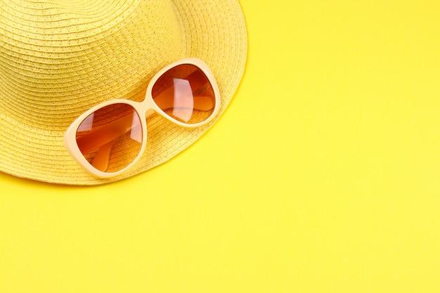Hut, sonnenbrille auf einem gelben pastellhintergrund. Premium Fotos