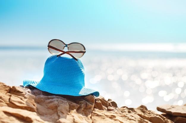 Hut und sonnenbrille auf dem felsen, klares meer. ferienkonzept der reise. Premium Fotos