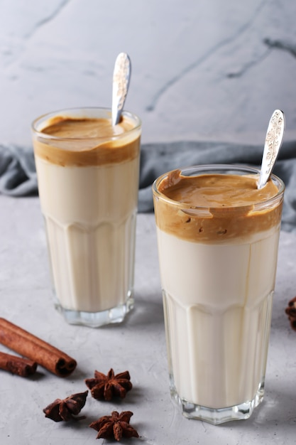 Iced dalgona kaffee in hohen gläsern mit gewürzen auf hellgrauem betontisch Premium Fotos