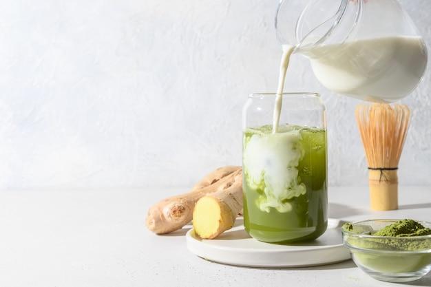 Iced green matcha tee und milch in latte glas auf weißen tisch gießen. platz für text. nahansicht. horizontale ausrichtung. Premium Fotos