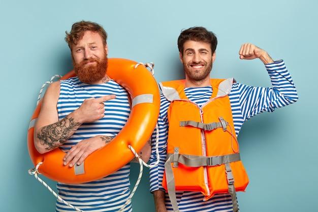 Ich bin froh, dass der stolze männliche schwimmer den arm hebt und muskeln zeigt, die bereit sind, menschen das leben auf dem wasser zu retten Kostenlose Fotos
