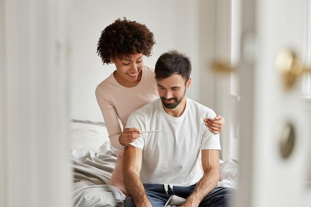 Ich bin froh, dass eine dunkelhäutige frau ihrem freund das ergebnis einer schwangerschaft zeigt, ein lächeln auf den gesichtern hat, in freizeitkleidung gekleidet ist und in einem gemütlichen schlafzimmer posiert. familienpaar freut sich gemeinsam über die nachricht von einer schwangerschaft. Kostenlose Fotos