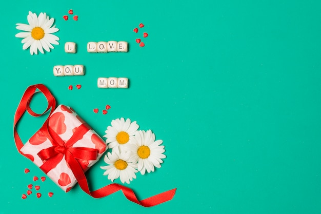 Ich liebe dich mama titel in der nähe von weißen blumen und geschenkbox Kostenlose Fotos