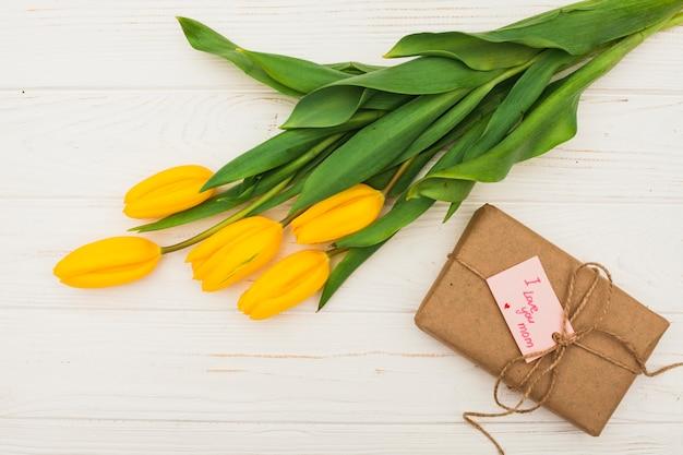 Ich liebe dich mom inschrift mit geschenk und gelben tulpen Kostenlose Fotos