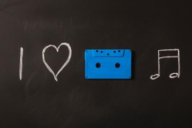 Ich liebe musikikonen, die mit blauer kassette auf tafel gezeichnet werden Kostenlose Fotos