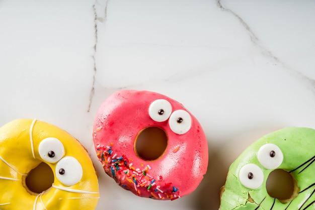 Ideen für kinderfestlichkeiten an halloween. bunte donuts in form von monstern mit augen, grün, gelb, Premium Fotos