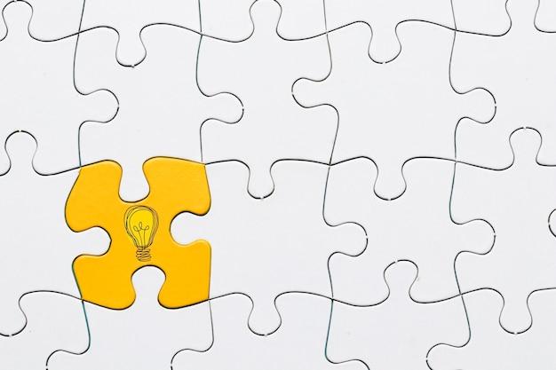 Ideenikone auf gelbem puzzlespielstück schloss an weißen gitterpuzzlespielhintergrund an Kostenlose Fotos