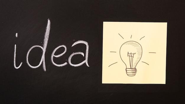 Ideentext geschrieben auf tafel mit der glühlampe gezeichnet auf klebrige anmerkung Kostenlose Fotos