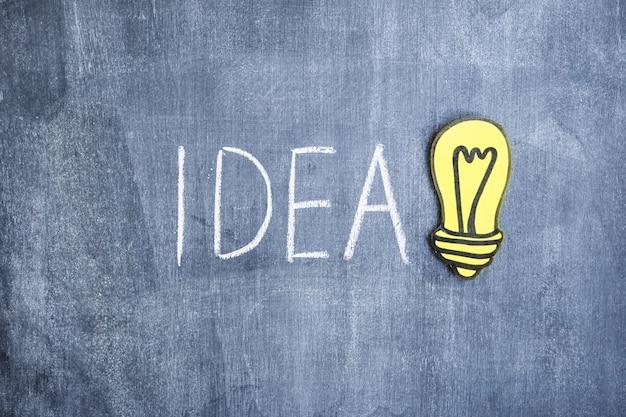 Ideentext geschrieben mit kreide mit glühlampe des papierausschnitts auf tafel Kostenlose Fotos